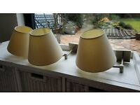 Three matching wall lamps, with shades and swivelling brass brackets
