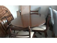 Dark mahogany oval dining table and 4 chairs. French polished finish. 2 pedestal supports.
