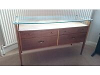 Retro elegant teak dressing table with brass fittings and floating glass top. Makers' label present.