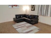 Ex-display Primo black leather corner sofa with chrome feet