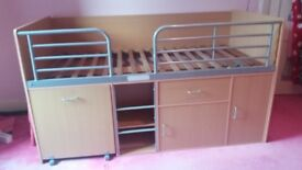 Childrens cabin bed with pull out desk, drawer and cupboards.