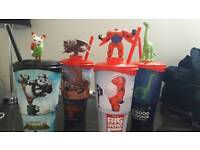 Assorted Disney and Dreamworks cups with figurines