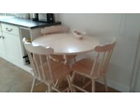 cream round kitchen table and four chairs