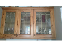 2 Honeyed pine kitchen wall display units with glass doors. (1 double plus 1 single)