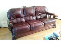 Leather three seater settee, arm chair and foot stool, on a carved wooden frame