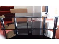 Black glass tv stand with chrome silver legs . Two shelves