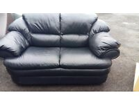 Black leather recliner armchair with a matching 2 seater sofa.