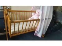 Rocking crib with mattress and drape pole.