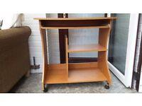 Wooden desk on wheels with keyboard shelf & additional shelf space underneath