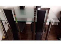 Glass dinning table with four black chairs