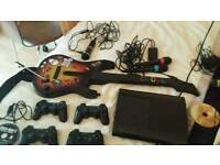 PS3 super slim 12GB with Buzz Quiz, Singstar Mics, Guitar Hero Guitar and 4 Controllers