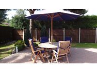 Neptune Solid Teak 1.4 Round Garden Patio Dining Table , 4 Reclining Chairs, Blue Cushions & Parasol