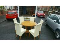 Very heavy oak wood circular dining room table with 6 heavy cream high back leather chairs
