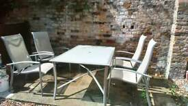 Large glass garden table and reclining chairs