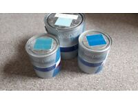 Unopened tins of blue/green/turquoise emulsion