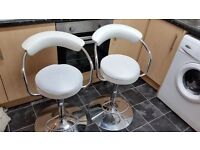 Two white faux leather reclining bar stools
