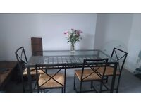 Black metal and glass dinning room table and four chairs
