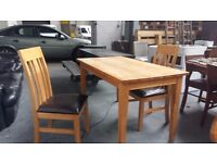 Very solid real oak table and 2 oak and leather chairs. Delivery is available if required.
