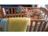 Immaculate pine cot from Mothercare with bedding and mobile.