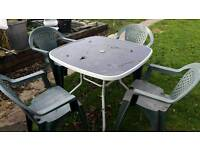 3 Outside plastic chairs with metal and glass table