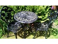 Ornate metal garden table and two chairs
