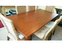 Solid wooden dining table and 6 wicker chairs