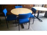 Circular office desk with 4 blue cushioned chairs