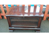 brown wood tv unit with glass door and pull out shelves