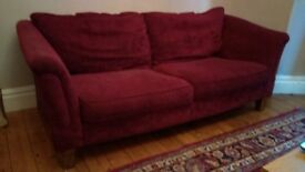 Two large deep red fabric sofas