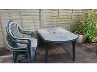 Plastic garden table with 4 accompanying chairs.