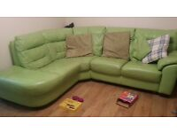 green corner sofa and large round swivel chair