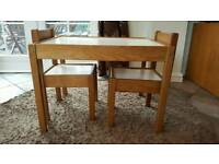 Childrens wooden table and two chairs.