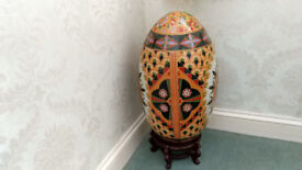 Large ceramic egg ornament with a wooden stand.
