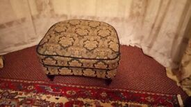 Low stool, fully upholstered, on 4, turned mahogany legs with brass castors