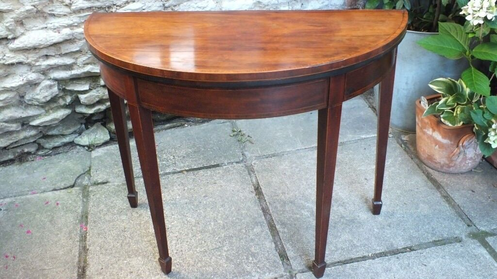 an early 19th century mahogany half moon fold over card table in