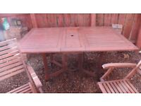 Large hardwood foldable table and six chairs with heavy duty covers.
