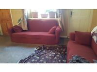 Sofa settee covered with fabric to protect perfect condition red and cream underneath