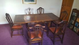 Solid dark oak extendable dining table and six chairs