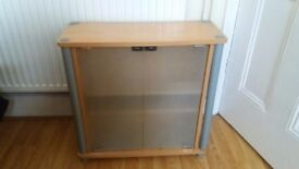 Small wooden cabinet/cupboard to store DVDs etc. Frosted glass doors which push shut.
