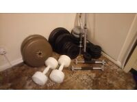 Weights set - 124kg of plates (mostly iron) with barbell, dumbells and curl bar