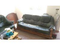 Two matching green leather three seater sofas