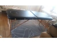 Portable black leather massage table
