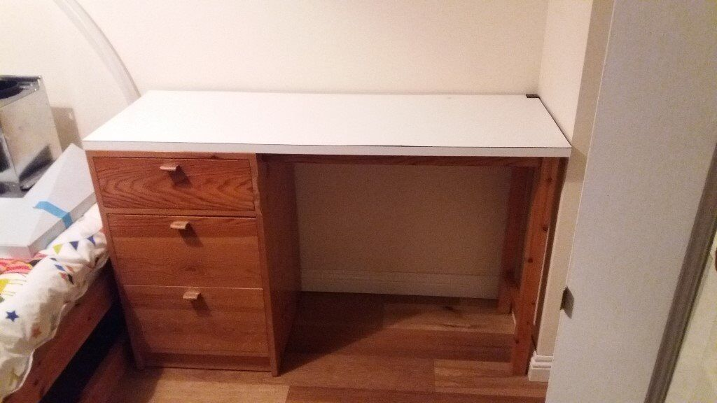 Desk with three wooden drawers and white worktop