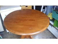 Round extending dining table. No chairs.