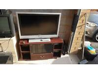 (TV only powers on no picture) Free to collect TV stand and TV for repairs
