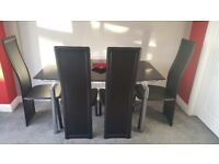 Black glass extendable dining table with 4 black chairs
