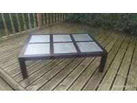 Black/brown large coffee table with glass top.
