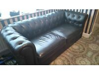 Black leather chesterfield.