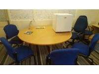 Large round office table and blue chairs. Table as new, chairs slightly worn, also small fridge.