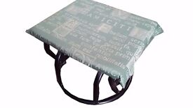 A rocking footstool with a green cover with Latin text